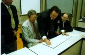 Sims signing official documents at the opening of the Haikui museum.